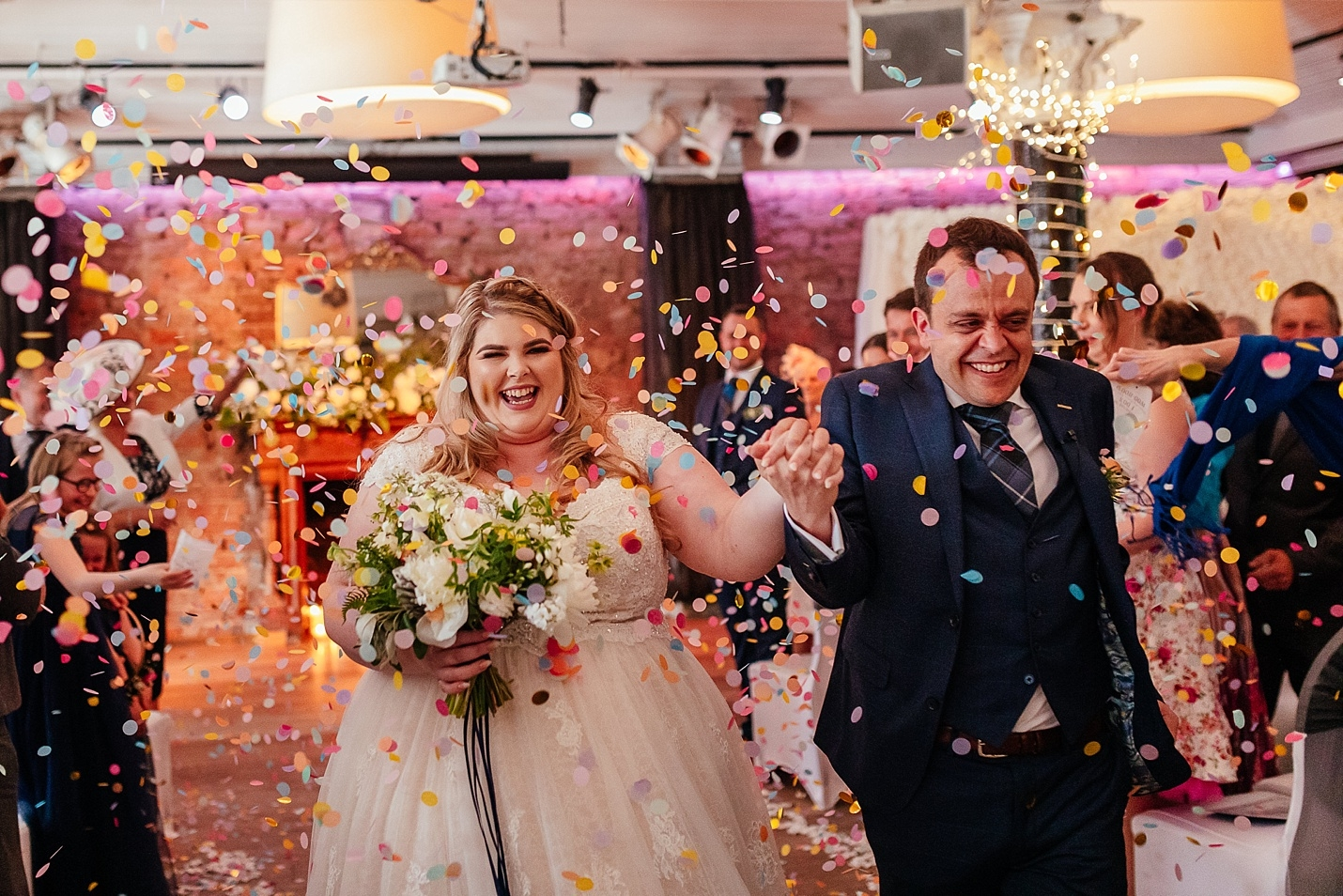 Bride and groom exit ceremony as colourful confetti is thrown
