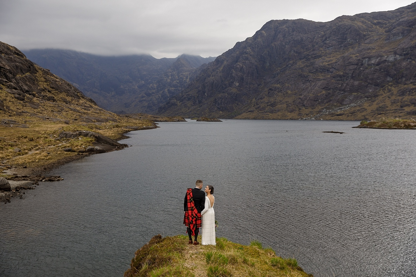Bride and groom look out over Loch Coruisk at their Isle of Skye wedding